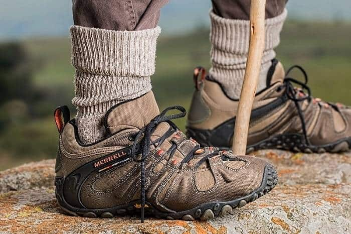 socks makes shoes comfortable and men stand on stone put a tracking shoes with socks