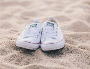 white converse on sunlight sand