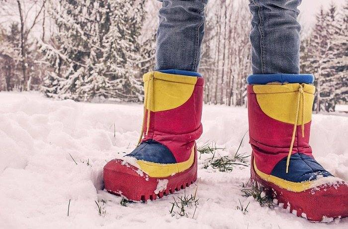 Red and Yellow Insulated shoe on snow