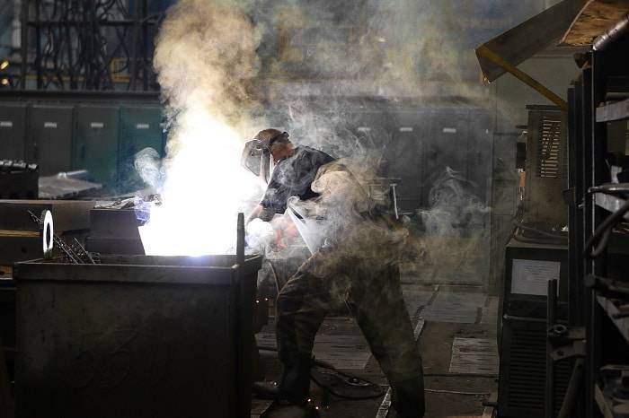 a man working in garage with protective shoes, gloves and eye glass