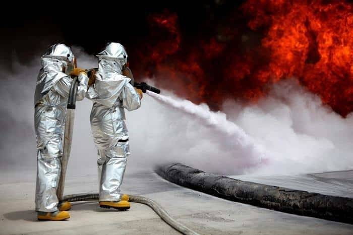two fire fighter wear fire resistant shoes and fire protecting suit to controlled danger