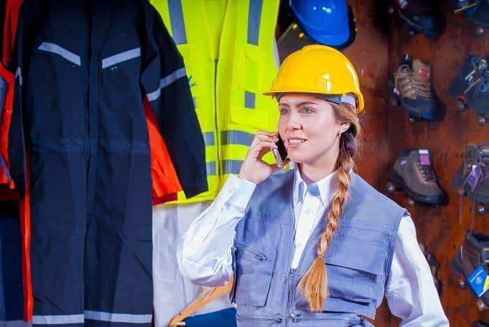 woman in gray vest with yellow hard hat in front of safety footwear and equipment storage