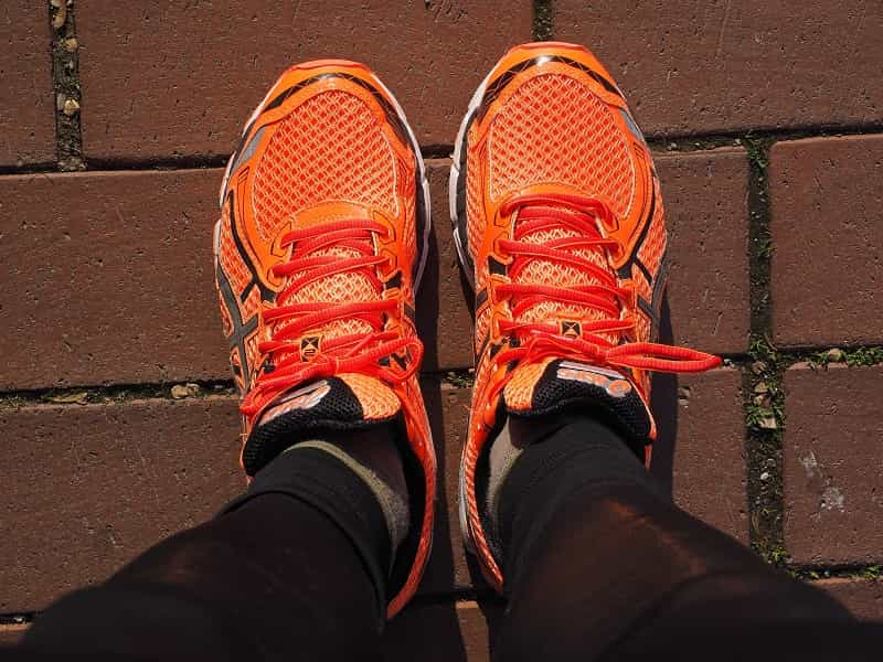 A beginner runner standing a orange running shoes that have great fitting and comfortable