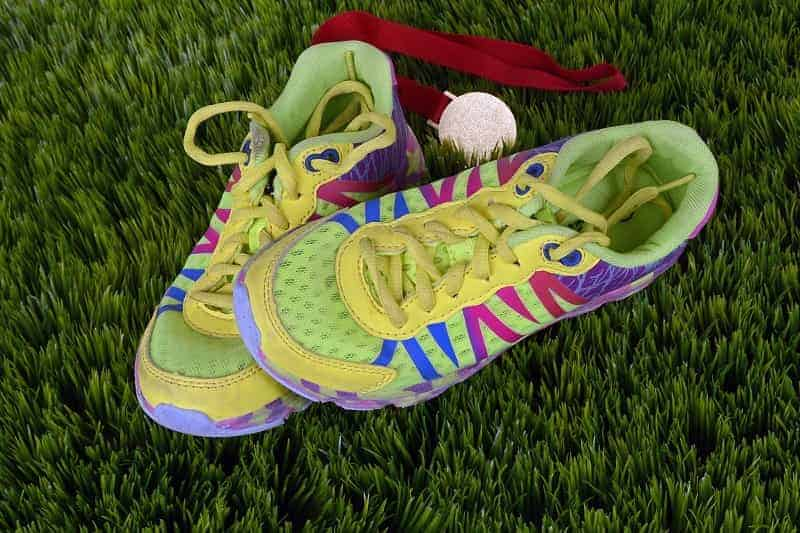 A pair of durable running shoes with a winning medal on green grasses